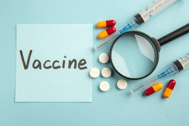Vista superior de inyecciones de antivirus con píldoras y con covid dibujo sobre una superficie azul laboratorio ciencia pandemia covid- virus vacuna hospitalaria color salud