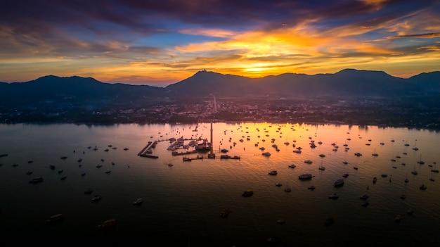Vista superior de la isla tropical, vista aérea del puerto al atardecer, paisaje con barco.