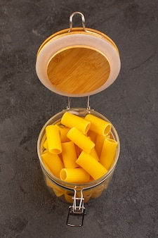 Una vista superior italiana pasta seca amarilla cruda dentro del recipiente aislado en la oscuridad