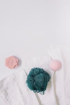 Vista superior de jabón; bomba de baño lufa y servilleta en superficie blanca