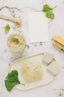 Vista superior de jabón; sal; piedra pómez; cepillo; hoja de ginkgo y tarjeta en blanco sobre fondo de mármol