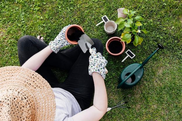 Vista superior jardinero sentado y plantación