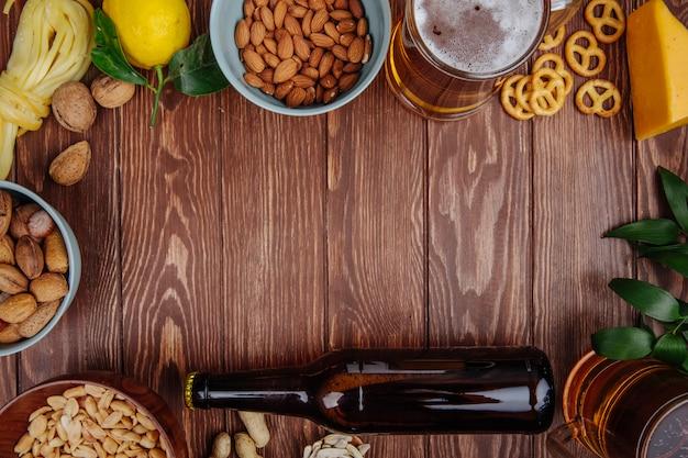 Vista superior de una jarra de cerveza con varios aperitivos salados en madera rústica con espacio de copia