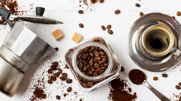 Vista superior jarra con granos de café orgánicos en la mesa