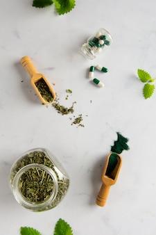Vista superior jarra con hierbas y cápsulas sobre la mesa
