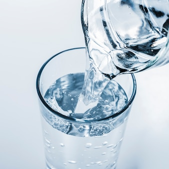Vista superior jarra llenando vaso de agua