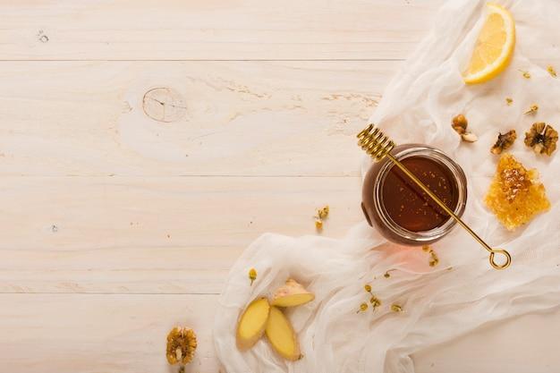 Vista superior jarra de miel con comida y cuchara de miel