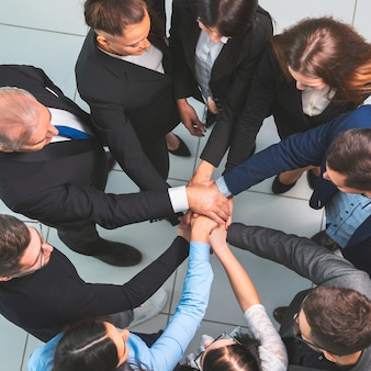Vista superior. jefe y equipo empresarial haciendo un montón de manos. el concepto de unidad