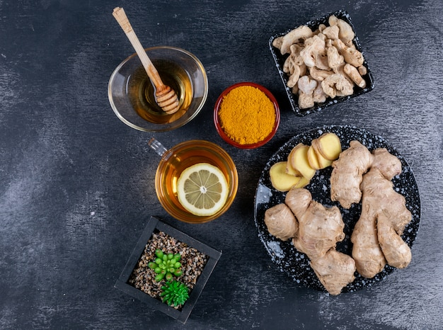 Vista superior de jengibre en tazones y plato con miel, una taza de té con limón, rodajas de jengibre y polvo sobre fondo oscuro con textura. horizontal