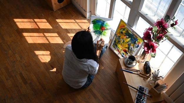 Vista superior joven artista dibujando una pintura al óleo mientras está sentado en el piso de madera.