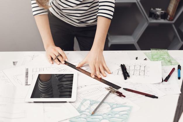 Vista superior de la joven y atractiva chica estudiante de arquitectura en camisa casual a rayas y jeans negros de pie cerca de la mesa, sosteniendo la regla y el bolígrafo en las manos haciendo dibujos, viendo películas en la mesa digital, gett