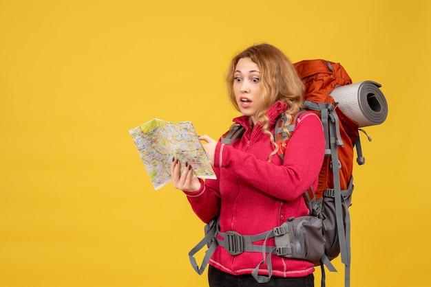 Vista superior de la joven chica viajera sorprendida en máscara médica sosteniendo y mirando el mapa