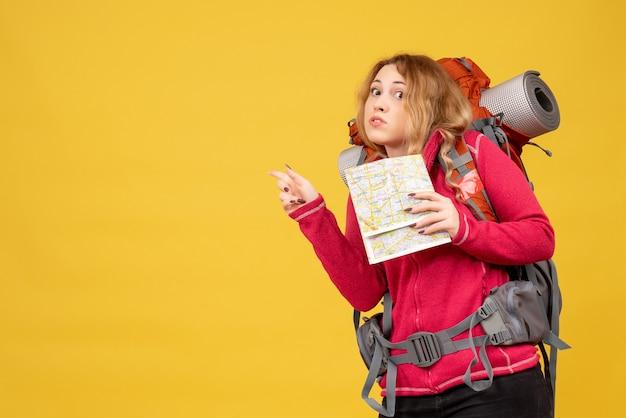 Vista superior de la joven confusa viajera con máscara médica recogiendo su equipaje y sosteniendo el mapa apuntando hacia atrás