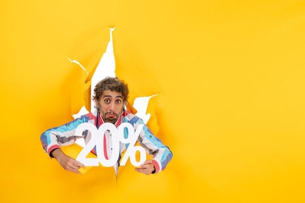 Vista superior del joven decepcionado que muestra el veinte por ciento en un agujero rasgado en papel amarillo