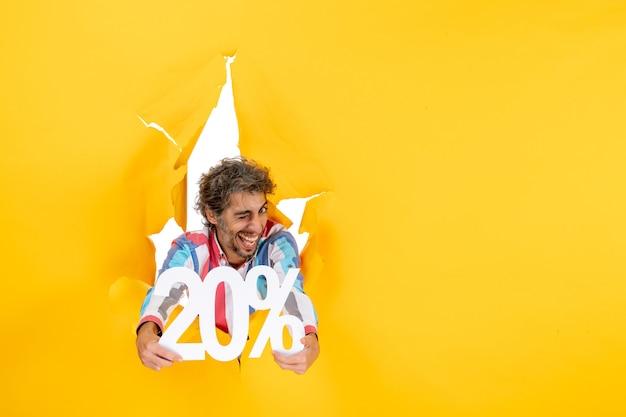 Vista superior del joven divertido que muestra el veinte por ciento en un agujero rasgado en papel amarillo