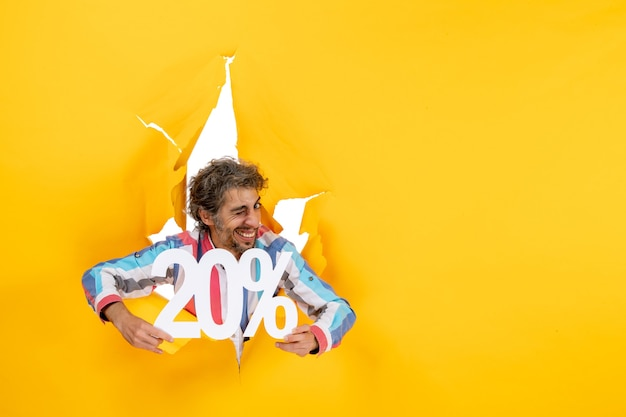 Vista superior del joven emocional que muestra el veinte por ciento en un agujero rasgado en papel amarillo