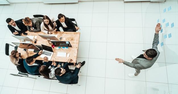 Vista superior joven empresario de pie en medio de una oficina espaciosa
