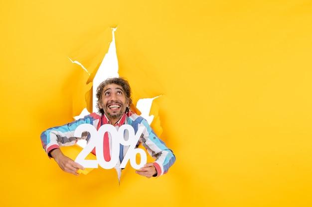 Vista superior del joven feliz mostrando veinte por ciento y mirando hacia arriba en un agujero rasgado en papel amarillo