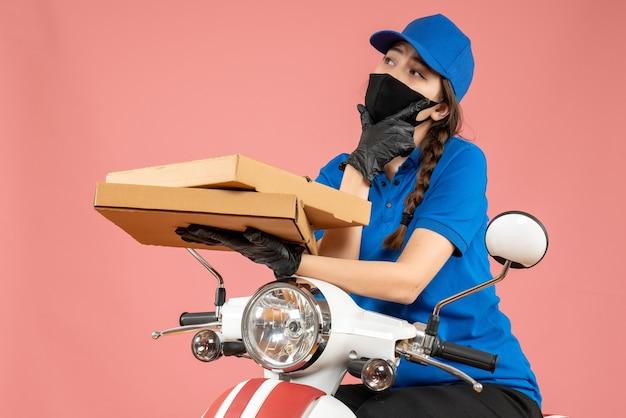 Vista superior del joven mensajero femenino reflexivo con máscara médica y guantes sosteniendo cajas en melocotón pastel