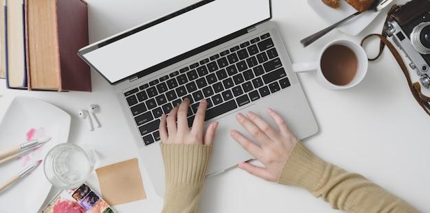 Vista superior de joven mujer escribiendo en la computadora portátil en un acogedor espacio de trabajo con suministros de oficina