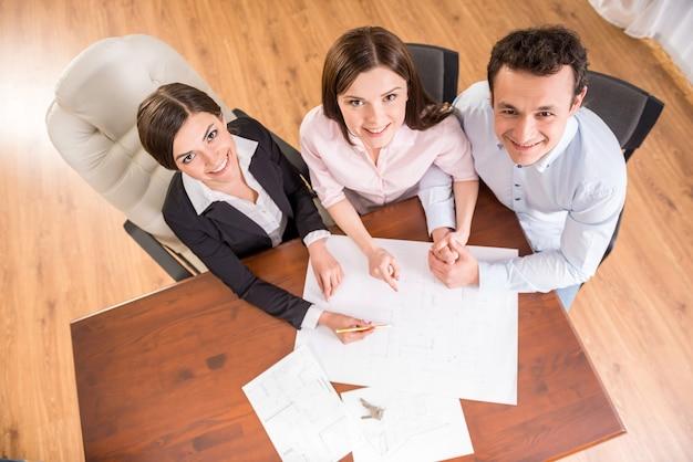 Vista superior de la joven pareja y agente inmobiliario femenino.
