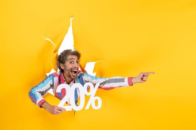 Vista superior del joven positivo mostrando veinte por ciento y apuntando algo en el lado izquierdo en un agujero rasgado en papel amarillo
