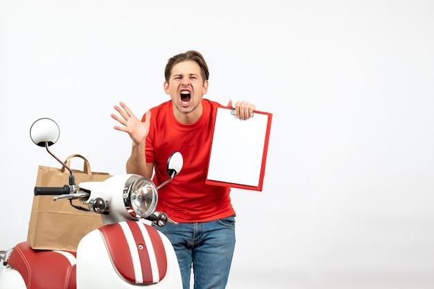 Vista superior del joven repartidor nervioso en uniforme rojo de pie cerca de scooter mostrando documento haciendo gesto de anteojos gritando en la pared blanca