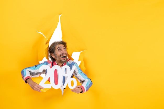 Vista superior del joven sonriente y feliz mostrando veinte por ciento y mirando hacia arriba en un agujero rasgado en papel amarillo