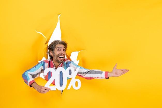 Vista superior del joven sonriente mostrando veinte por ciento y apuntando algo en el lado izquierdo en un agujero rasgado en papel amarillo