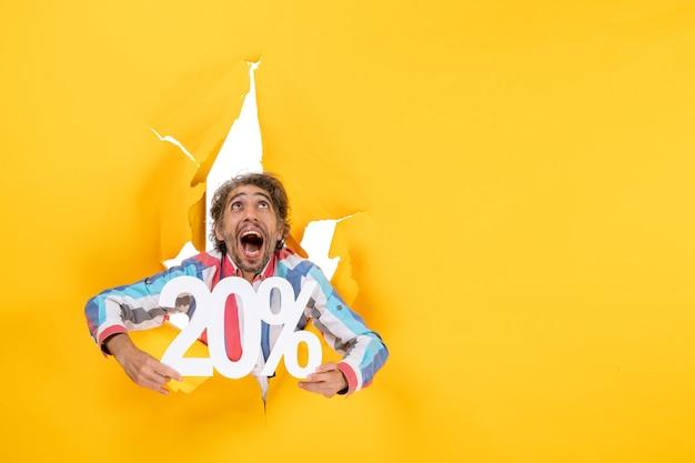 Vista superior del joven sonriente mostrando veinte por ciento y mirando hacia arriba en un agujero rasgado en papel amarillo