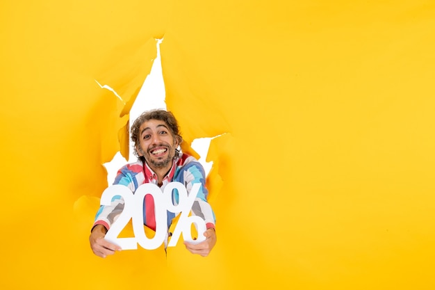 Vista superior del joven sonriente que muestra el veinte por ciento en un agujero rasgado en papel amarillo