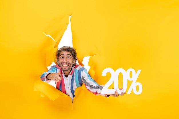 Vista superior del joven sonriente sosteniendo veinte por ciento y apuntando algo en un agujero rasgado en papel amarillo