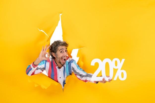 Vista superior del joven sonriente sosteniendo veinte por ciento y haciendo gesto de anteojos en un agujero rasgado en papel amarillo