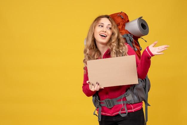 Vista superior de la joven sonriente viajera recogiendo su equipaje de pie