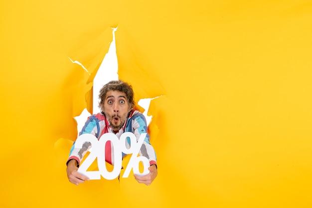 Vista superior del joven sorprendido y emocional que muestra el veinte por ciento en un agujero rasgado en papel amarillo