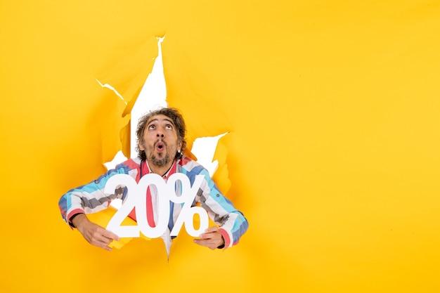 Vista superior del joven sorprendido mostrando veinte por ciento y mirando hacia arriba en un agujero rasgado en papel amarillo