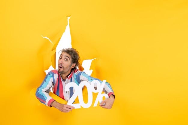 Vista superior del joven sorprendido que muestra el veinte por ciento en un agujero rasgado en papel amarillo