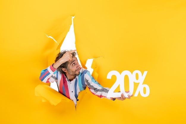 Vista superior del joven sorprendido sosteniendo veinte por ciento y apuntando algo en un agujero rasgado en papel amarillo