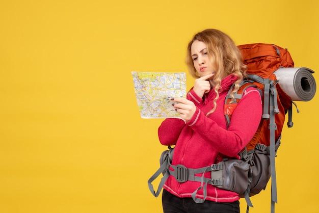 Vista superior de la joven viajera concentrada en máscara médica sosteniendo y mirando el mapa