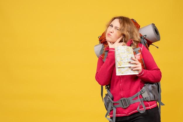 Vista superior de la joven viajera emocional preocupada en máscara médica recogiendo su equipaje y sosteniendo el mapa
