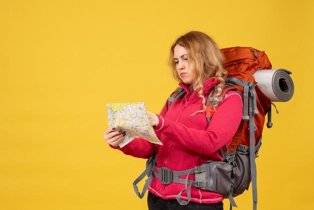 Vista superior de la joven viajera enfocada en máscara médica sosteniendo y mirando el mapa