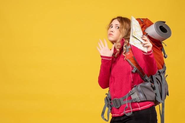 Vista superior de la joven viajera insegura incierta con máscara médica recogiendo su equipaje y sosteniendo el mapa