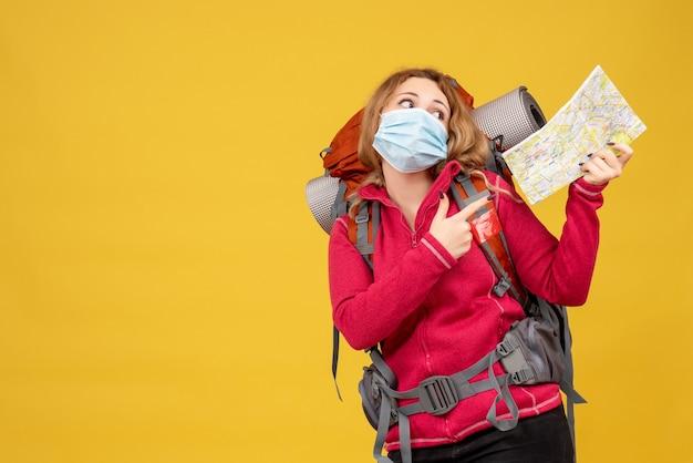 Vista superior de la joven viajera con máscara médica recogiendo su equipaje y mostrando el mapa