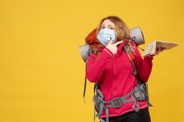 Vista superior de la joven viajera en máscara médica recogiendo su equipaje y señalando el mapa