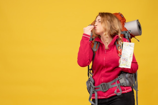 Vista superior de la joven viajera con máscara médica recogiendo su equipaje y sosteniendo el mapa haciendo un gesto perfecto