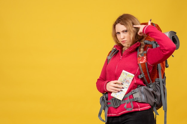 Vista superior de la joven viajera con máscara médica recogiendo su equipaje y sosteniendo el mapa en pensamientos profundos