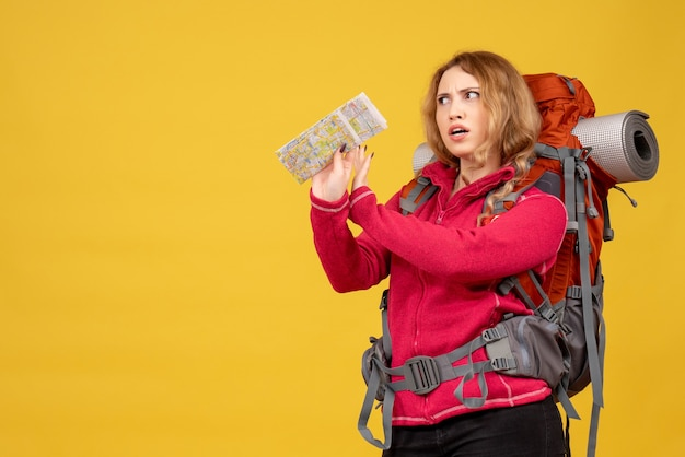 Vista superior de la joven viajera preguntándose en máscara médica recogiendo su equipaje y sosteniendo el mapa