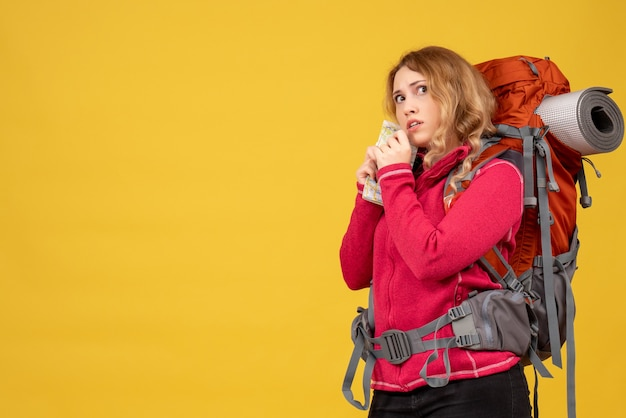 Vista superior de la joven viajera preocupada en máscara médica recogiendo su equipaje y sosteniendo el mapa