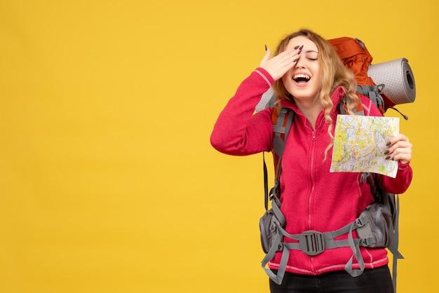 Vista superior de la joven viajera satisfecha con máscara médica sosteniendo y mostrando el mapa disfrutando de su éxito