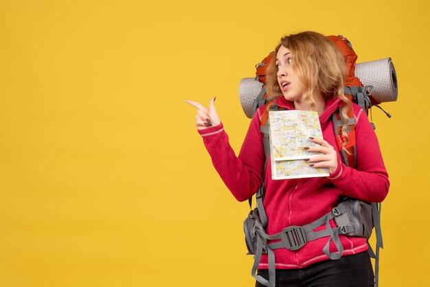 Vista superior de la joven viajera sorprendida en máscara médica recogiendo su equipaje y sosteniendo el mapa apuntando hacia atrás